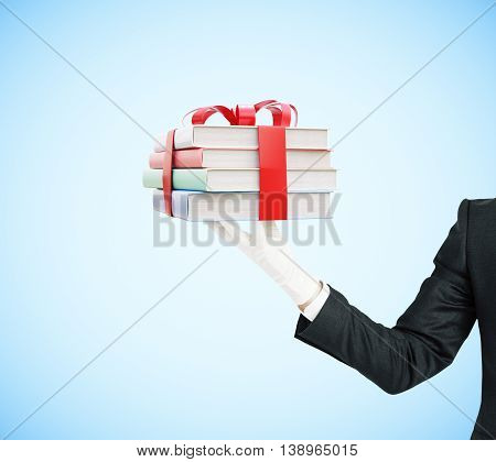 Businessman hand holding stack of colorful book tied up with a ribbon on blue background. 3D Rendering