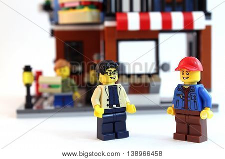 Colorado, USA - July 16, 2016: Studio shot of LEGO minifigure guys talking in front of a LEGO brick building, shot isolated on white background.