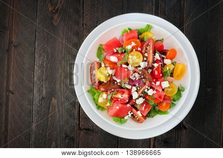 Watermelon And Mixed Tomato Salad With Feta Cheese Overhead View On Dark Wood