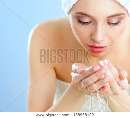 Young female washing her face with clear water.