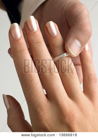 Man Putting Diamond Ring On Woman's Finger