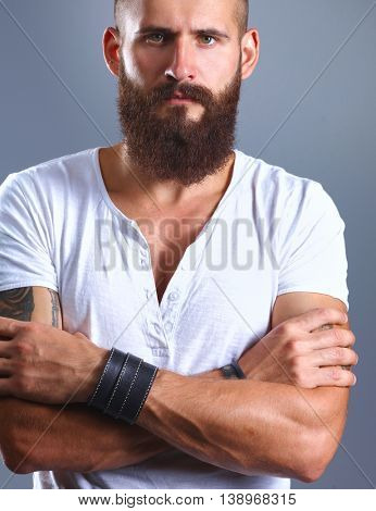 Portrait of handsome bearded man standing with crossed arms, isolated on grey background