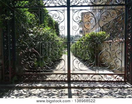 openwork gate at a country residence, the shade on a summer day