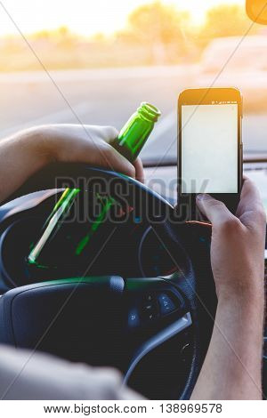 Drunk young man driving a car with a bottle of beer and mobile phone. Don't drink and drive concept. Don't text and drive. Driving under the influence, Driving while intoxicated.