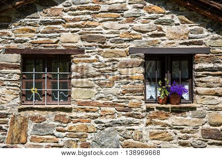 two windows on a stone chalet with violet flowers