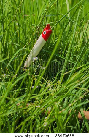 Plastic white and red fishing lure for spinning in grass - concept of a rural getaway and fishing, vertical.