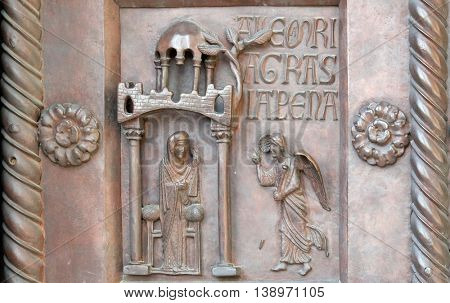 PISA, ITALY - JUNE 06, 2015: Annunciation of the Virgin Mary on the San Ranieri gate of the Cathedral St. Mary of the Assumption in Pisa, Italy on June 06, 2015