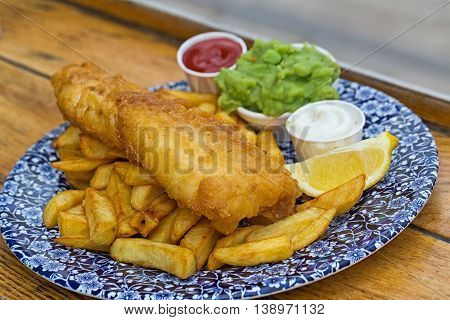 fish and chips served in mediterranean restaurant against the sea british food