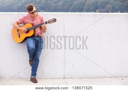 Sound music voice passion talent concept. Man with guitar leaning on wall. Young male guitarist playing on instrument.