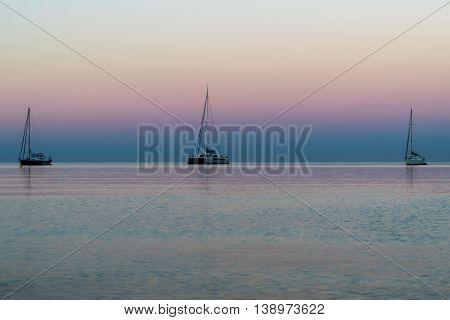 Three sail boats on the horizon at sunrise