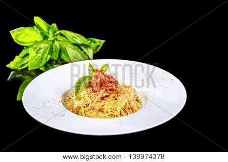Spaghetti Carbonara with Basil on a black background isolated.