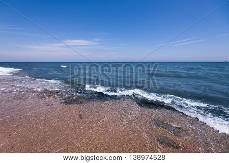 Seascape of sand shore and waves of Caspian sea