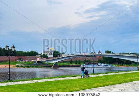 VELIKY NOVGOROD RUSSIA - JULY 15 2016. Novgorod Kremlin with footbridge and embankment near the Volkhov river in summer cloudy day - summer city view. Selective focus at the Kremlin