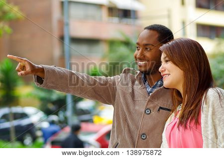 Interracial happy charming couple wearing casual clothes interacting for camera in outdoors urban environment.