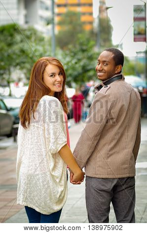 Interracial happy charming couple wearing casual clothes walking holding hands, turns around heads for camera in outdoors urban environment.