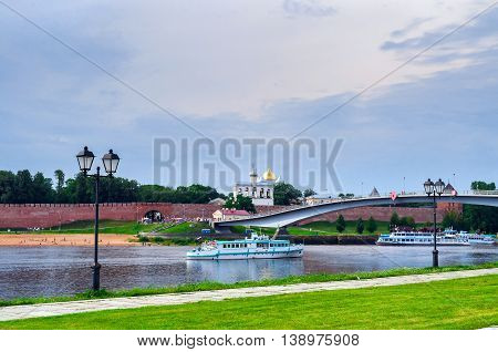 VELIKY NOVGOROD RUSSIA - JULY 15 2016. Novgorod Kremlin with footbridge and pleasure boat floating the Volkhov river in summer cloudy day - architecture landscape. Selective focus at the Kremlin
