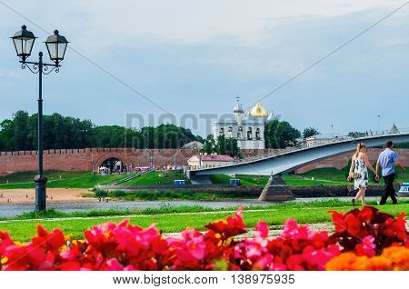 VELIKY NOVGOROD RUSSIA - JULY 15 2016. Novgorod Kremlin and pedestrian bridge across the Volkhov river in summer sunny day with flowerbed at the foreground. Selective focus at the Kremlin