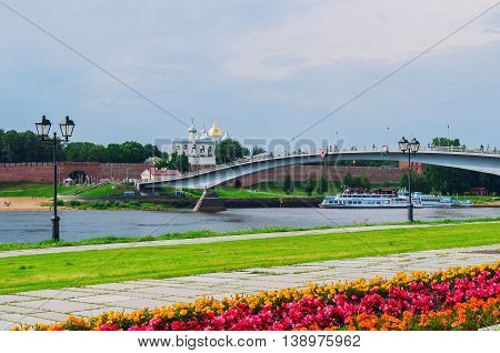 VELIKY NOVGOROD RUSSIA - JULY 15 2016. Novgorod Kremlin with footbridge and embankment near the Volkhov river in summer cloudy day. Selective focus at the Kremlin