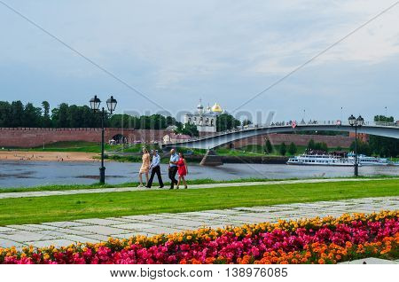 VELIKY NOVGOROD RUSSIA - JULY 15 2016. Novgorod Kremlin and embankment along the Volkhov river in summer sunny day with flowerbed at the foreground. Selective focus at the Kremlin