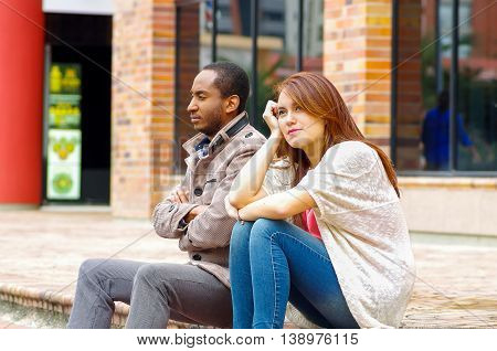 Interracial upset couple sitting on steps in front of building, simulating argument for camera.