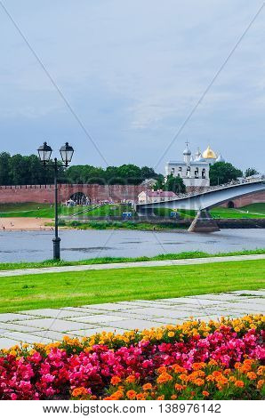VELIKY NOVGOROD RUSSIA - JULY 15 2016. Novgorod Kremlin with footbridge and embankment near the Volkhov river in summer cloudy day - architecture summer view. Selective focus at the Kremlin