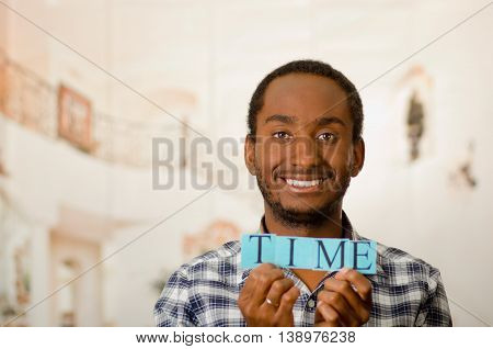 Headshot handsome man holding up small letters spelling the word time and smiling to camera.