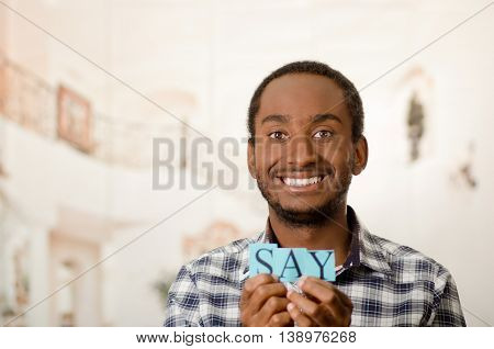 Headshot handsome man holding up small letters spelling the word say and smiling to camera.