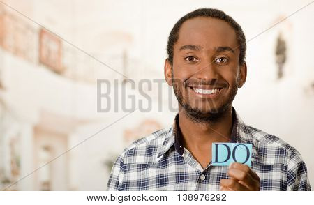 Headshot handsome man holding up small letters spelling the word do and smiling to camera.