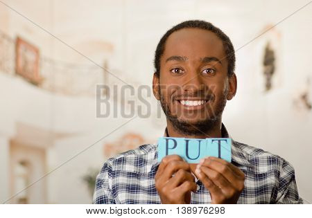Headshot handsome man holding up small letters spelling the word put and smiling to camera.