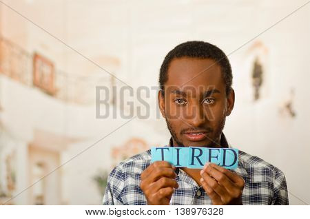Headshot handsome man holding up small letters spelling the word tired and looking to camera.