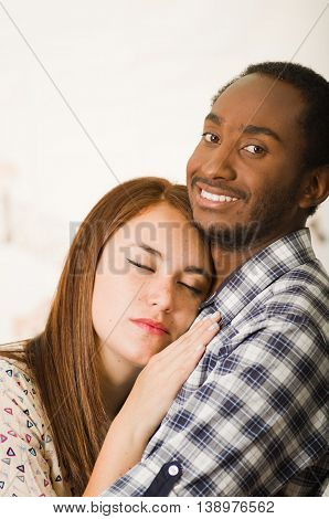 Interracial charming couple wearing casual clothes posing while embracing intimately, she has eyes closed and him smiling, profile angle with white studio background.
