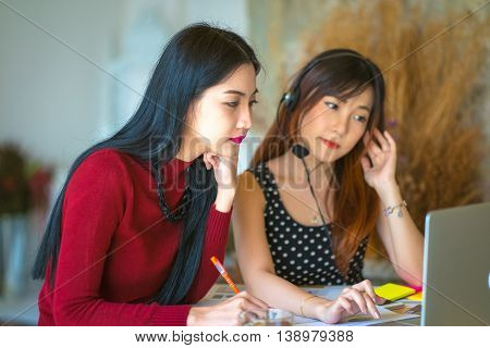 The Asian Young Business Woman Use Laptop Sitting At Wooden Table Of Modern Coffee Shop