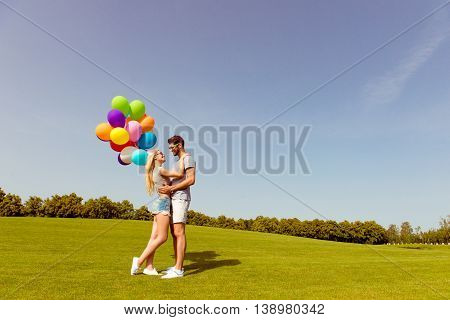 Two Happy Young Lovers With Balloons Embracing In The Park