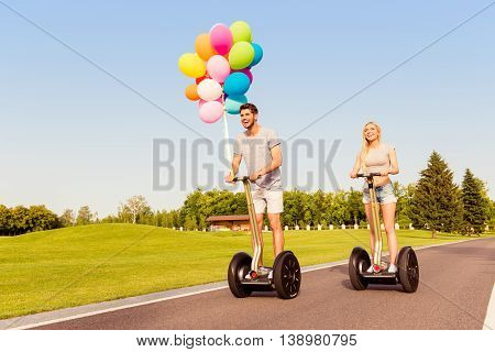 Two Happy Lovers With Balloons Having Tour On Segway In Park