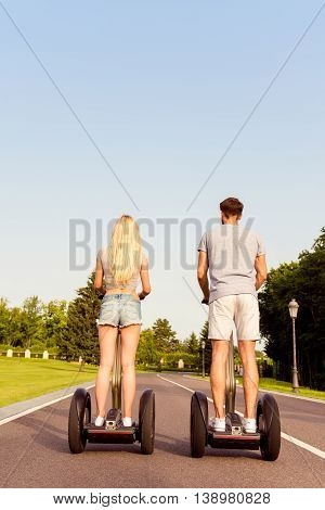Back View Of Man And Woman Having Weekend And Riding Segway