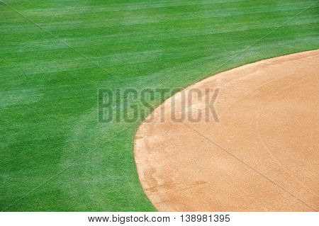 close up on baseball playing field with green grass and dirt