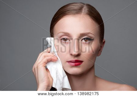 Beautiful woman removing makeup from her face skin care concept