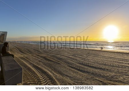 Unidentified person with hoodie watching beach sunrise in Surfers Paradise