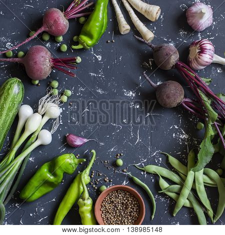 Fresh vegetables - beets peppers green beans onion garlic zucchini on dark background. Top view
