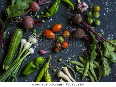 Beets zucchini peppers onion garlic green beans beans tomatoes parsnips parsley - fresh vegetables on a dark background. Raw ingredients. Top view