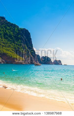 Beach of Cleopatra with sea and rocks of Alanya peninsula, Antalya, Turkey. Beautiful landscape of tourist destination with high green cliff and Castle of Alanya.