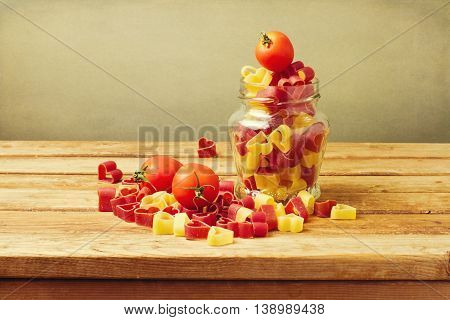 Colorful heart shape pasto with tomatoes on wooden table