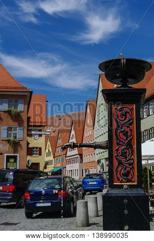 Dinkelsbuhl, Germany - August 28, 2010: Street water pump in medieval town Dinkelsbuhl one of the archetypal towns on the German Romantic Road.