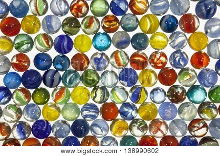 Colorful vintage toy marbles macro on white.