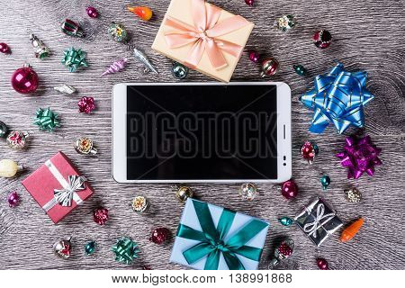 Tablet computer with blank black screen among christmas gifts on wooden background. Holiday image for New Year and Christmas. Vintage texture for design uses. Banner template for web ads.