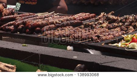 Bacon wrapped around sausage on a barbecue to cook at a fair ground.