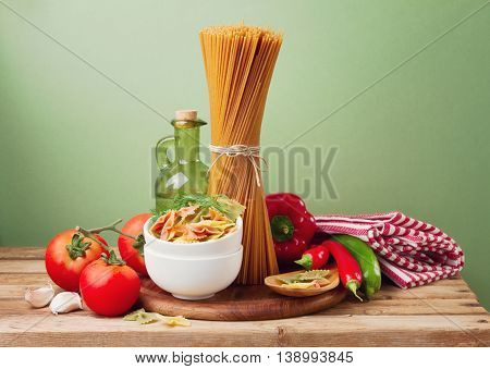 Still life with whole wheat pasta on wooden table over green background
