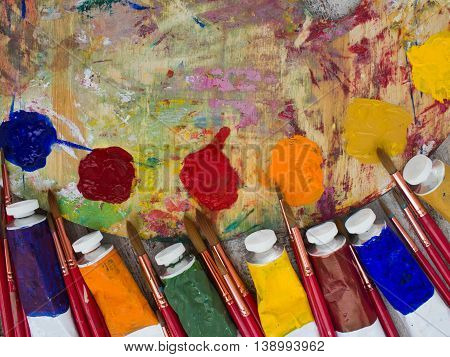 Brushes, paint, palette, painted canvas on wood background