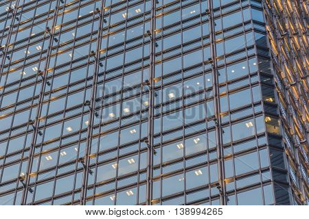 Glass windows pattern on the building at night with some lights on.