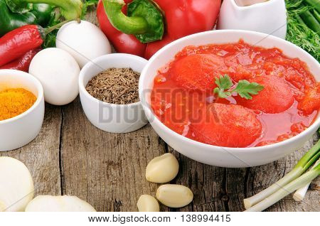 Different ingredients for cooking healthy and tasty food. Tomatoes in own juice spicy seasoning pepper onion garlic olive oil and eggs on a wooden table with copy space